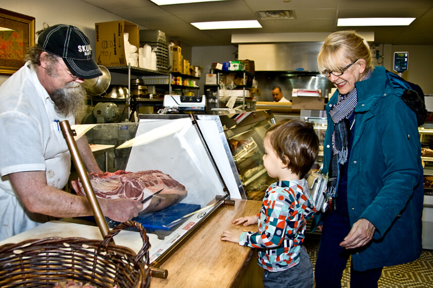 mom and son buy meat from butcher