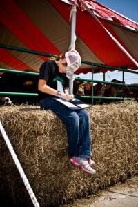 boy sits on hay bale