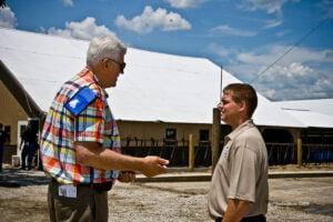 Justin Kilgus and tourist outside barns