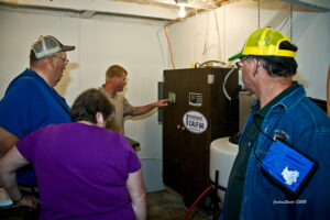tour group looks at calf feeder