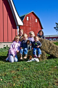 kilgus kids in front of red barn with baby goats
