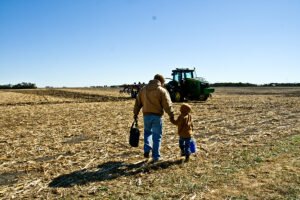 matt kilgus and young son holding hands in field
