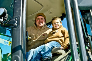 matt kilgus and son smiling in tractor